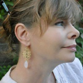 boucles d'oreilles Moscou mises en valeur sur modèle, longues avec une perle goutte en verre opaline sur une rosace baroque dorée tres fine