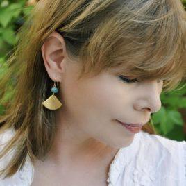 photo des boucles d'oreilles Beijing portée, un eventail stylisé et rétro doré à l'or fin surmonté d'une perle en verre tchèque bleu-vert